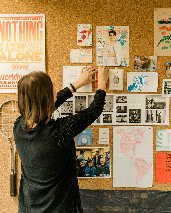 Photo of Focus Lab team member, Charisse, pinning something onto a cork board wall.